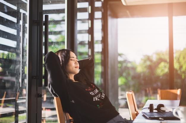 彼女の椅子でリラックスし、オフィスの窓からの眺めを楽しむ女性