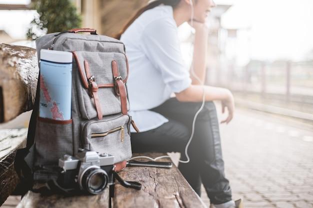 Женщина - турист, сидящий, чтобы слушать музыку, чтобы ждать поезда в вокзале.