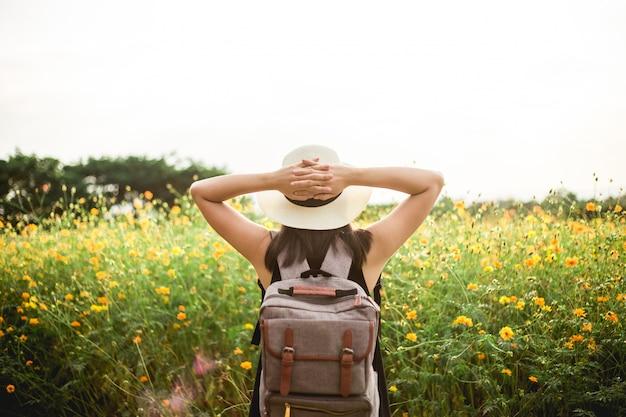 美しい花畑を歩いている若い女性の背面図山の後ろがあります。