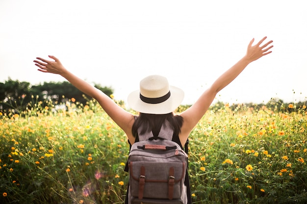 美しい花畑に出て歩く若い女性の背面図