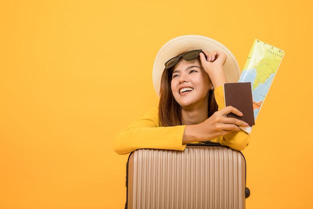 夏のカジュアルな服、地図とパスポートを保持している女性の女性、