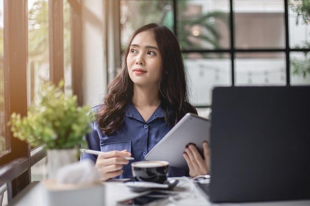 アジアの女性はタブレットを運ぶノートを持っていて、喫茶店で笑顔で考えています。