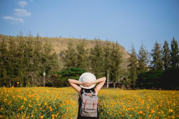 バックパックと素晴らしい山々を見ている女性旅行者。