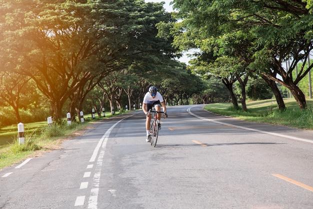 アジア人男性、サイクリストは夕方に運動しています。