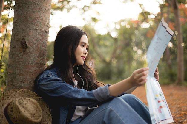 Азиатские женщины видят карты со шляпой на закате.