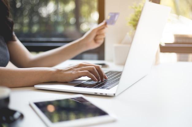 女性の手はクレジットカードを持っていて、ラップトップを通してオンラインで購入しています。