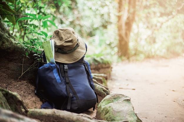地図と帽子が地面に付いたバックパック