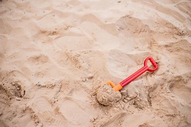 子供用ビーチおもちゃ砂の中の小さなシャベル。