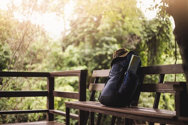 マップとベンチに帽子のバックパック