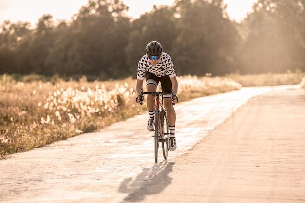 アジア人男性のサイクリストが夕日に開いた道で自転車に乗って。