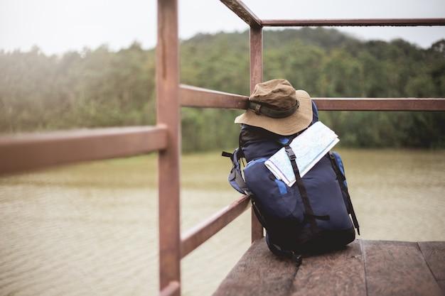 彼のバックパックでドックに座っている男