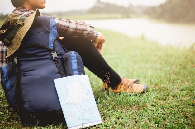 彼のバックパックで草の中に座っている男