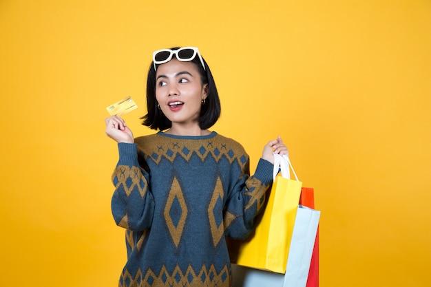 カラフルな紙袋とクレジットカードを保持しているメガネのアジア女性