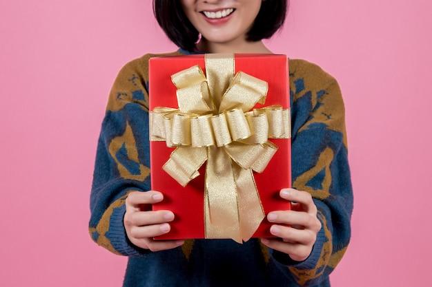 ピンクの背景にギフトを持つアジアの女性。