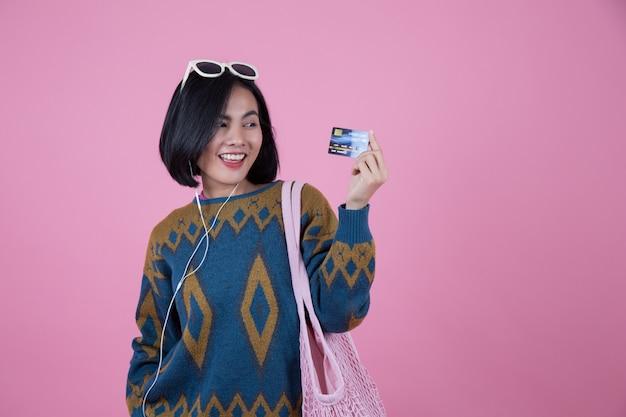 サングラス、ピンクのバッグ、ヘッドフォンでクレジットカードを示すアジアの女性。