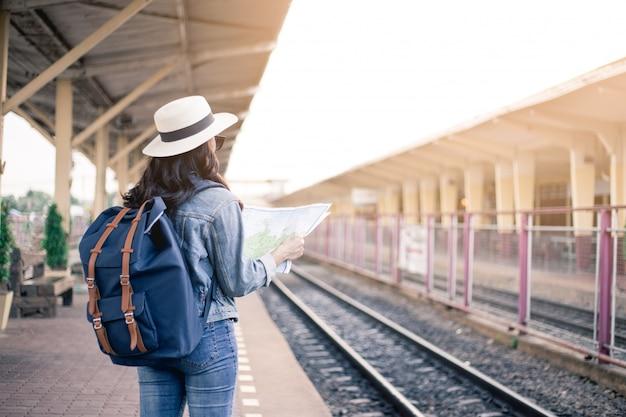 アジアの女性観光客の裏側、黒い眼鏡の袋を運んで、帽子をかぶって、駅で地図を持っています。