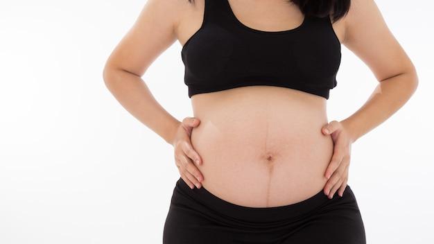 Беременная азиатская женщина с белой предпосылкой