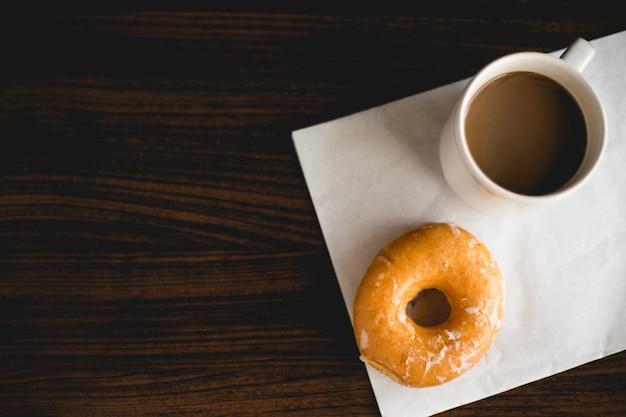 ドーナツと木製のテーブルの上のコーヒー