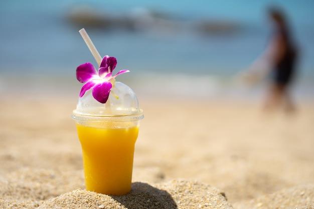 オレンジのスムージーと夏のビーチ