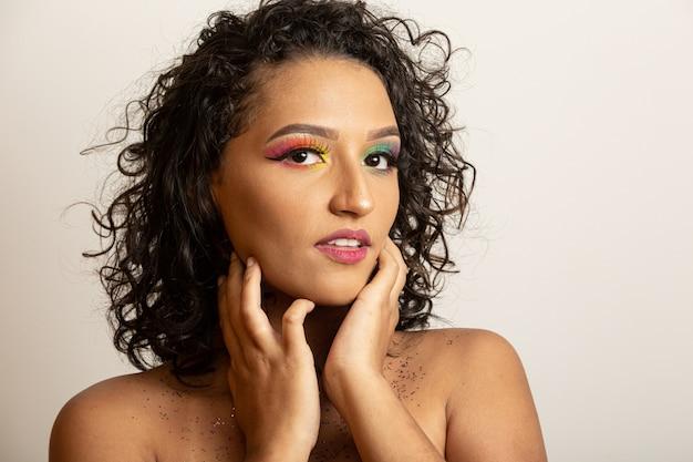 巻き毛とカラフルなメイクと美容ファッションモデルの女の子。カメラに笑顔アフロ女性