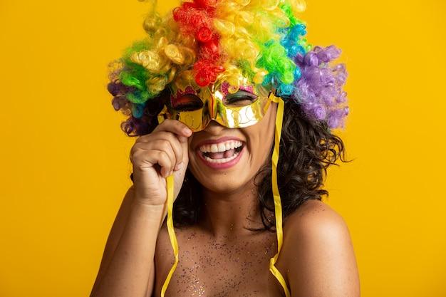 カーニバルの夜に身を包んだ美しい女性。カラフルなかつらとマスクとカーニバルを楽しむ準備ができて笑顔の女性