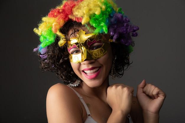 カーニバルの夜に身を包んだ美しい女性。カラフルなかつらとマスクでカーニバルを楽しむ準備ができて笑顔の女性