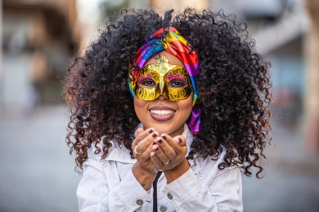カーニバルパーティー。紙吹雪を吹く衣装でブラジルの巻き毛の女性