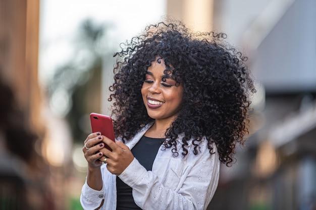Молодая вьющиеся волосы негритянка ходить с помощью мобильного телефона. текстовые сообщения на улице. большой город.