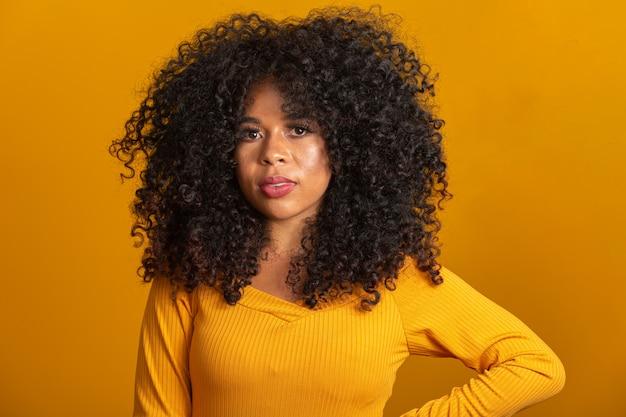 Молодая афроамериканская женщина с вьющимися волосами и улыбкой. милая афро девушка с вьющимися волосами улыбается