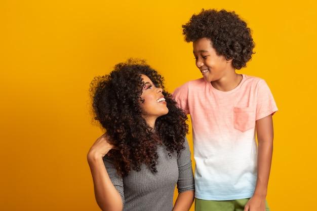 幼児の息子を持つ若いアフリカ系アメリカ人の母の肖像画。黄色の壁。ブラジルの家族。