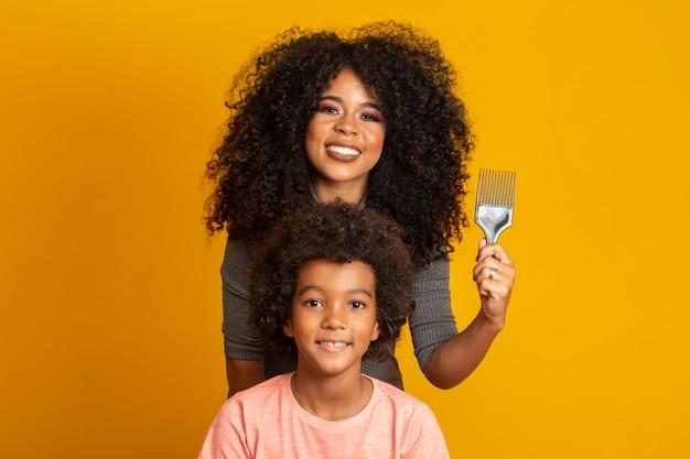 分離された髪をとかす若いアフリカ系アメリカ人。カールした髪をとかすためのフォーク。黄色の壁。