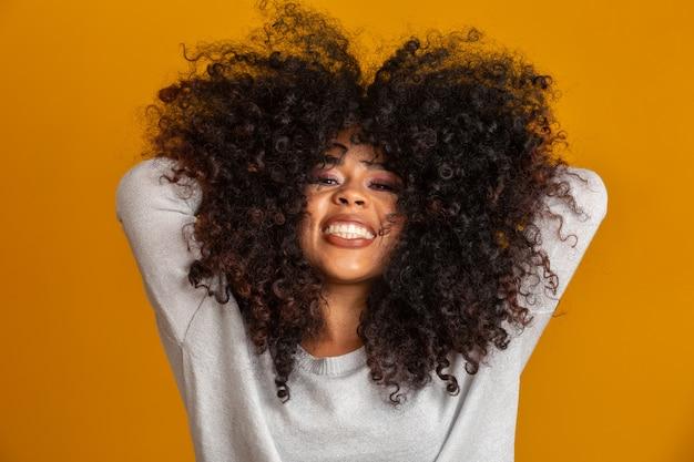 アフロの髪型と魅力のメイクとアフリカ系アメリカ人の女性の美しさの肖像画。ブラジルの女性。混血。巻き毛。髪のスタイル。黄色の壁。