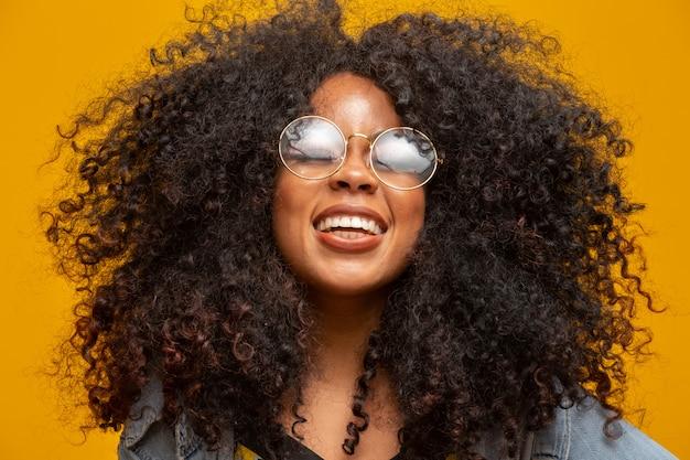 Портрет красоты афроамериканца с стеклами и афро стилем причёсок на желтой стене. бразильская молодая женщина.