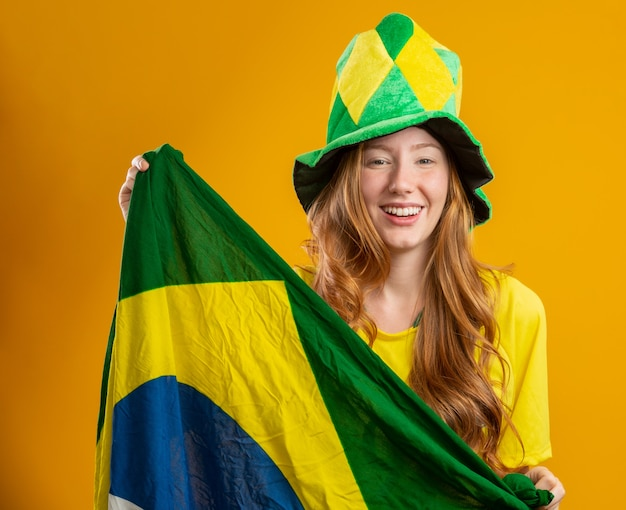 Сторонник бразилии. бразильский рыжий женщина вентилятор празднует на футбол, футбольный матч бразилия цвета. носить футболку, флаг и веерную шляпу.