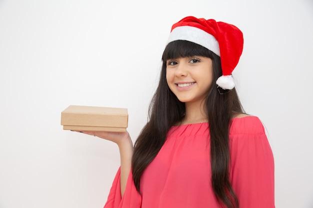 クリスマスプレゼントを持ってサンタ帽子の若い女