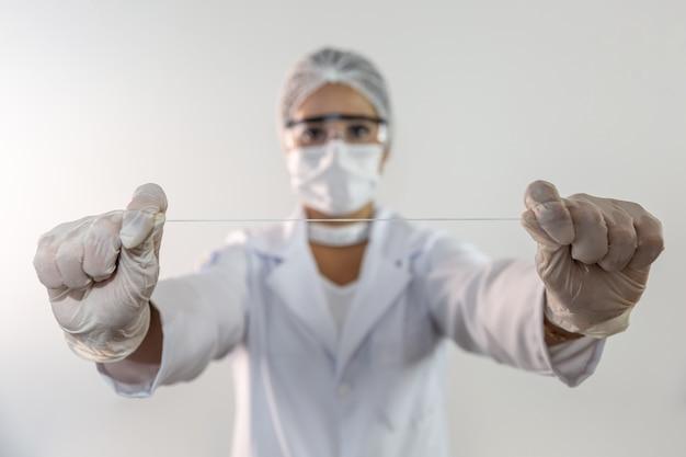 フロスの切れ端を提示する歯科医、歯をきれいにするための新しい技術の開発