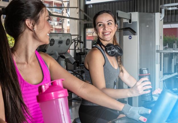 美しい女性がジムでトレーニングします。明るくモダンなジムでトレッドミルで運動する若い女性の友人の美しいグループ。