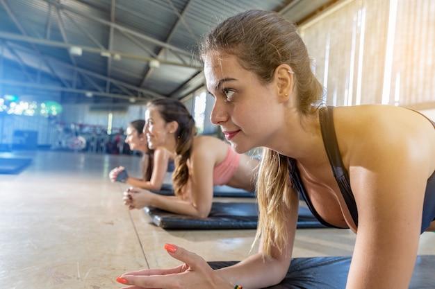 板をしている美しい若い女性は、ジムで運動します。腹を失うための運動。あなたの体が夏の間ひびを入れているようにしてください。