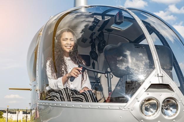 離陸前にヘリコプターのコックピットで女性のパイロット。若い女性のヘリコプターのパイロット。
