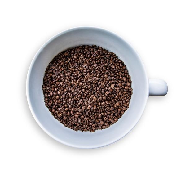 白い空のコピースペースの背景に分離された大きなセラミックマグカップでコーヒーの種子。