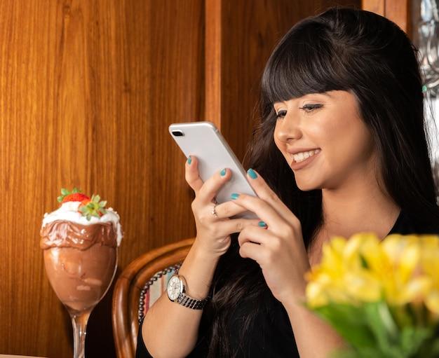 Женщина фотографируя вкусное мороженое белое смешивает клубнику с умным телефоном.