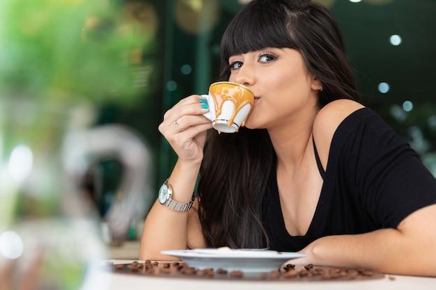 コーヒーテーブルを飲む女性。