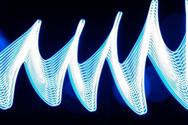 ライトを使った夜間のライトペインティング。黒い背景(写真)に抽象的な光の効果。