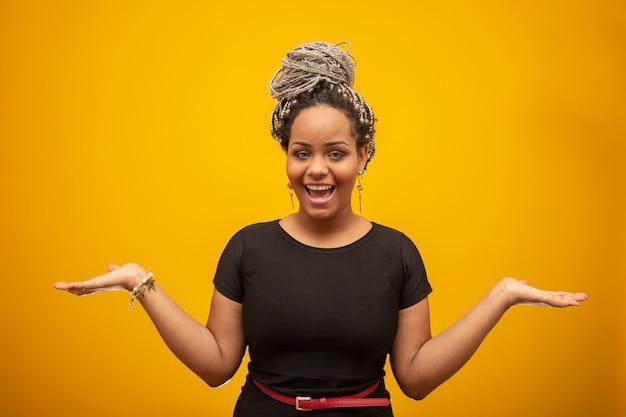 孤立した黄色の上の美しいアフリカ系アメリカ人の若い女性