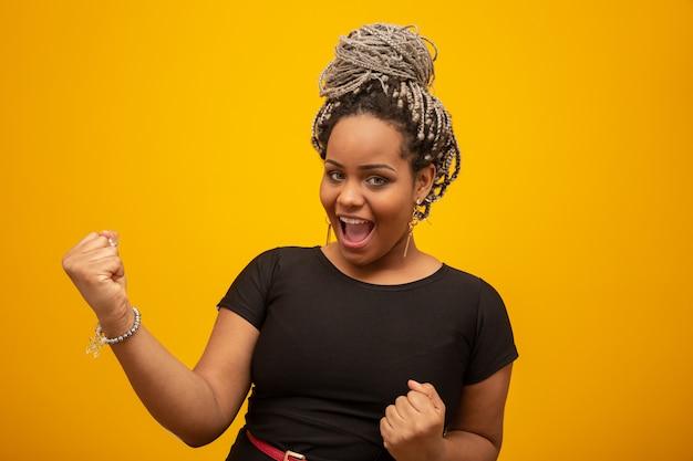 腕を持つ成功に興奮して孤立した黄色の上の美しいアフリカ系アメリカ人の若い女性は勝利の笑顔を祝って発生しました。美しい女性の半身像。勝者の概念