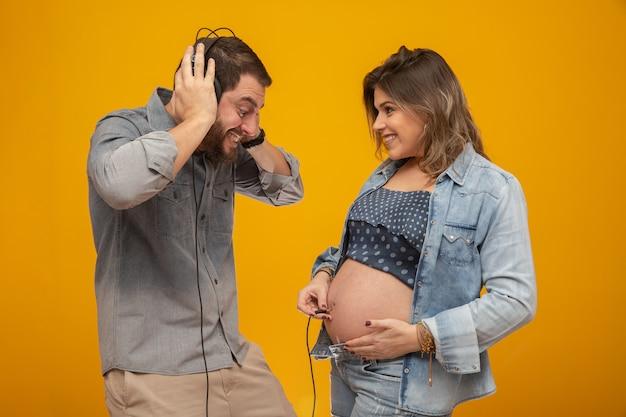夫は、息子が妻の腹をヘッドフォンで叩いているのを聞いて遊んでいます。