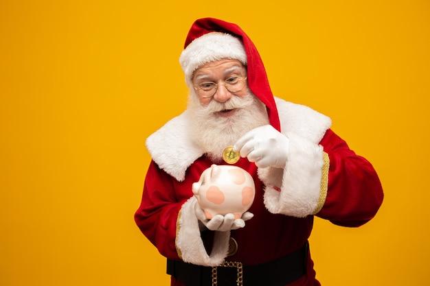 Санта клаус кладет монету в керамическую копилку