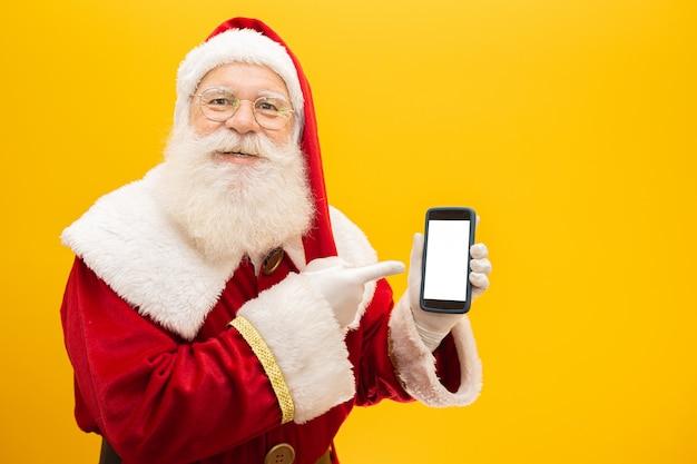 黄色の背景に携帯電話でサンタクロース
