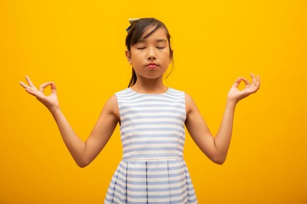 Азиатские дети мило или ребенок девочка в медитации с миром и расслабиться