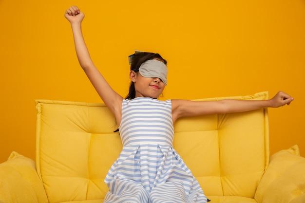 睡眠マスクが付いているソファーで寝ているアジアの子供